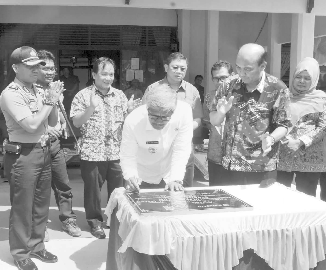 Governor H Sukarmis signs at the handover ceremony for the road asphalting. Image Source: Metro Riau