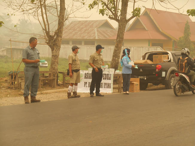 Asian Agri task force braves the haze to provide masks to motorists (Image source - GoRiau)