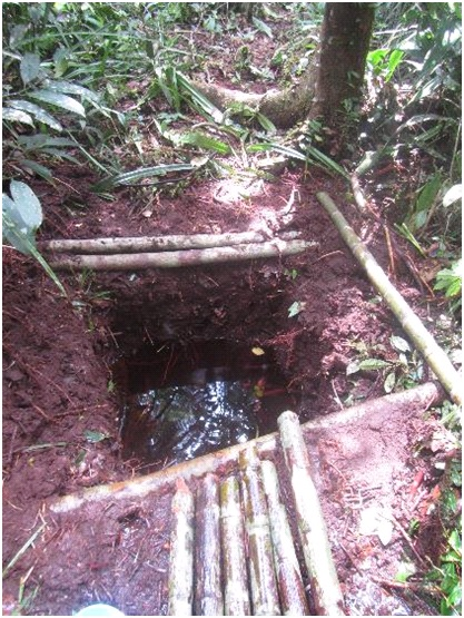 A pit dug into the peat soil to provide water.
