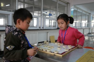 Primary school participants in a game of Chinese Chess at a competition co-organised by Asia Symbol
