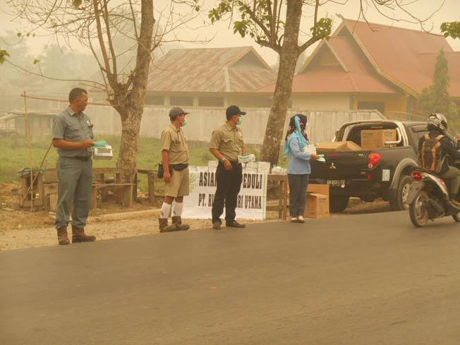 Asian Agri task force braves the haze to provide masks to motorists (Image source - GoRiau)