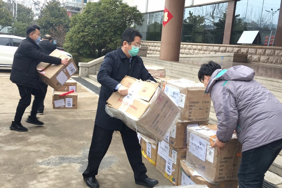 Staff from Asia Symbol help to move boxes of masks donated by the company.